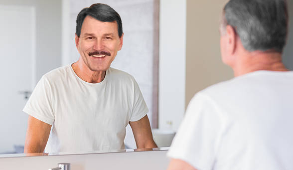 Mature man looking at his reflection in mirror